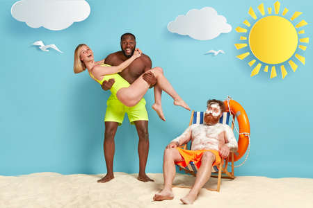 Photo of happy dark skinned guy carries girlfriend in swimsuit on hands, foolish together at beach, bearded red haired man smirked with sunblock cream looks at diverse couple. People at seaside