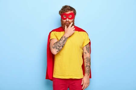 Sad serious superhero man touches thick red beard, wears mask and cloak, looks straightly at camera, thinks about making good things for other people and helping, isolated on blue background. Banco de Imagens