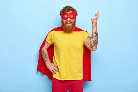 Irritated superhero raises arm and gestures with annoyance, has much work, wears special costume, pretends having supernatural power, outraged to fight with evil, poses indoor. Negative emotions