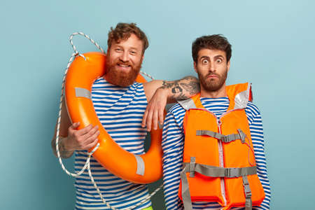 Happy red haired bearded male lifeguard and his colleague control safe swimming at sea, being glad and surprised, rescue people, use lifebuoy, wear striped jumper with blue stripes, life vest