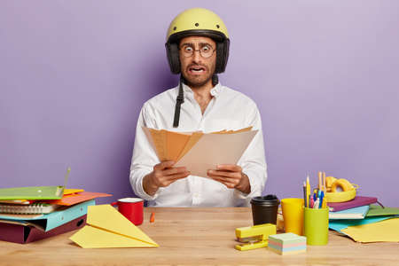 Emotive shocked male employee creats organisation plan, stares at papers, has to prepare main theses for startup project, wears protective helmet, sits at wooden desktop against purple background
