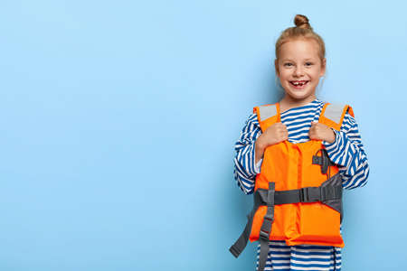 Watersport and children concept. Cute small ginger child has summer beach vacation, dressed in sailor jumper, orange life jacket for safe bathing in sea, has best holiday ever. Joy, season, kids Banque d'images