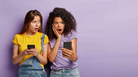Waist up portrait of multiethnic women stare with confusion at modern cellular, see distrubing message on screen, receive feedback from superstar, being speechless, pose indoor, blank space.