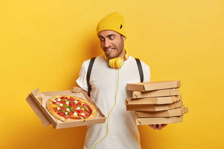 Handsome salesperson or courier represents delicious pizza, bites lips as looks at tasty junk food, holds stack of cardboard boxes, wears casual clothes isolated on yellow background. Delivery service