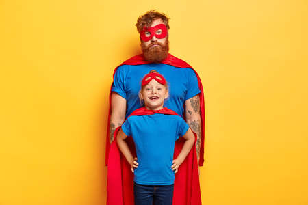 Studio shot of sad tired bearded daddy stands behind small daughter, wear superhero costumes with red capes and masks, being strong and brave, stand against yellow background. We save our world