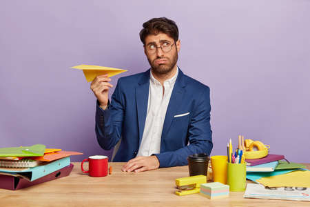 Portrait of young experienced entrepreneur thinks about main theses for business deal, being well dressed, holds paper plane, looks thoughtfully aside, drinks coffee, poses at desktop in cabinet