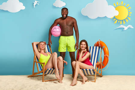 Two relaxed slim women in bikini rest on beach chairs, looks happily, cheerful black man with torso, carries beachball, suggests playing active game on beach. Mixed race people at seaside