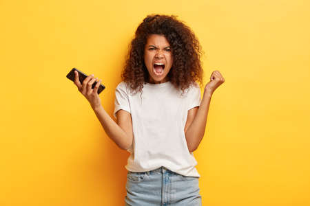 Outraged dark skinned woman raises clenched fist, holds modern cell phone, screams from annoyance as somebody read her message box, wears casual white t shirt and jeans, stands against yellow wall