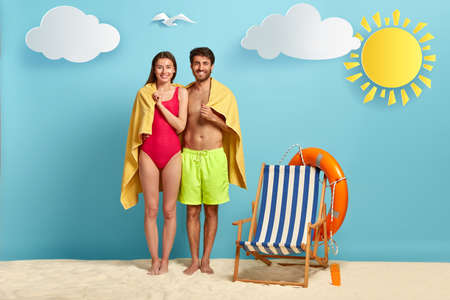 Travel and summer concept. Glad couple shelter under soft beach towel, dressed in swimsuit, hug together with love, empty deck chair with lifebuoy near, hide from sun, share intimate moment.
