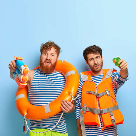 Friends with swimming equipment, use water pistols for battle, wear striped sailor jumpers, have fun at beach during good summer weather, pose against blue background, enjoy vacation at seaside