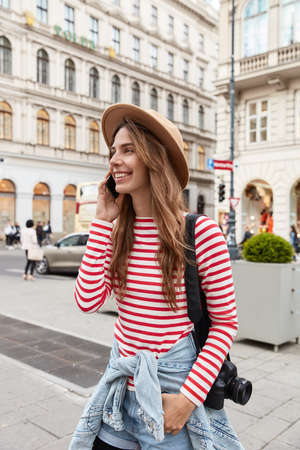 Photo of happy young female tourist in stylish outfit, strolls in city, has tour, carries photocamera on shoulder, talks on modern cellular, mock up area for advertising above, ancient building Stock Photo