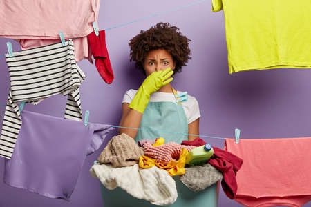 Shocked dissatisfied ethnic female housekeeper closes nose, smells dirty laundry from basket, busy with washing clothes during weekend, wears green rubber gloves and apron.