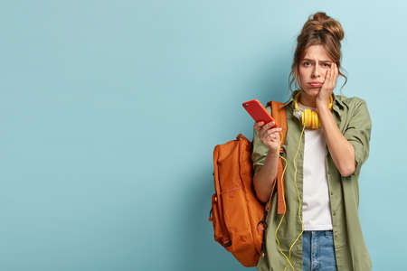 Puzzled gloomy young girl looks sadly at camera, cannot understand how to use new application, arent able to download song in playlist, has no internet connection, stands with rucksack over blue wall Foto de archivo
