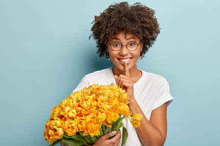 Young pretty lady with curly haircut, makes silence gesture, holds fore finger over lips, wears white t shirt, round spectacles, holds yellow tulips, looks at camera tells secret. Spring time, secrecy