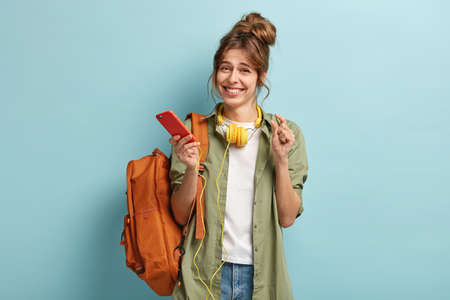 Pleased young European girl shows something very little with hand, enjoys free time and surfes internet on mobile phone, connected to stereo headphones, wears casual clothes, has backpack on shoulder