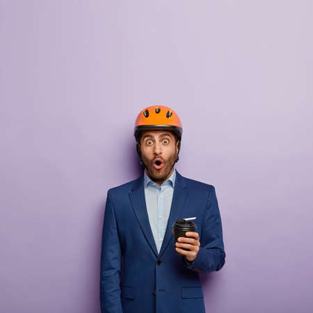 Shocked architect or foreman enjoys drinking coffee from disposable cup, wears builder hardhat, formal suit, surprised by bad news at work, stands against purple background with blank space. Stockfoto