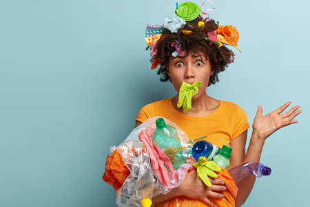 Scared frustrated Afro American woman overloaded with plastic, stuck mouth with rubber glove, has eyes popped out, worried by nature pollution, helps clean environment, free space aside for text