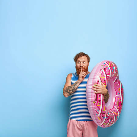 Secret red haired bearded man shows shush gesture, looks mysteriously aside, wears casual t shirt and shorts, holds rubber swim ring, gossips about future summer rest with friend, poses indoor