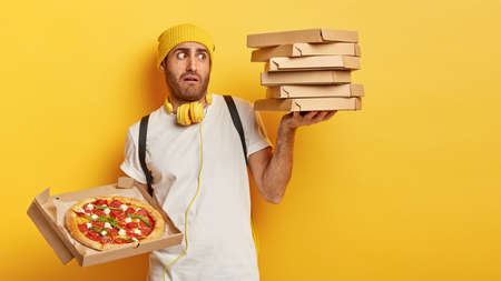 Busy overload service worker shocked to carry big stuck of carton boxes, delivers pizza to customers, works in pizzeria, dressed casually, works on weekends, isolated on yellow studio wall. Fast food