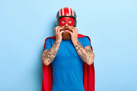 Scared nervous man looks with fear, wears helmet, red mask and cloak, prepares for flight, afraids of fighting evil, poses against blue background. People, emotions, reaction and supernatual power