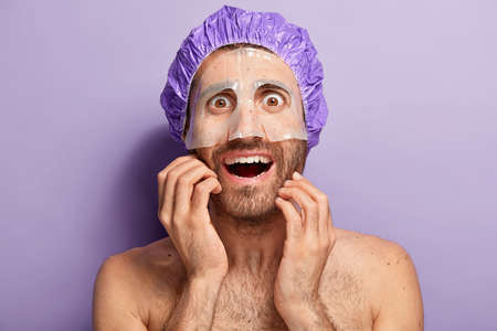 Naked happy man applies moisturize mask on face, wears violet shower cap, enjoys cosmetic skincare facial treatment, has brown bugged eyes, bare shoulders, stands indoor, looks surprisingly at mirror