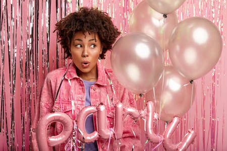 Photo of impressed dark skinned woman with make up looks surprisingly aside, being speechless, has bated breath, holds balloons, has tinsel on body, isolated over pink background. Monochrome. Фото со стока
