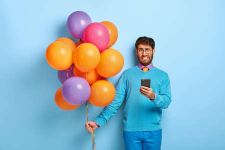Dissatisfied young man organises holiday on special occasion, unhappy to read bad news in internet, holds mobile phone, has spoiled party, finds out about tragedy with friend carries colorful balloons