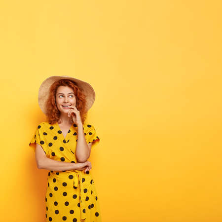 Elegant young foxy woman wears straw hat and polka dot summer dress, keeps hand near mouth, has pensive glad look, contemplates about something pleasant, poses against yellow wall, free space