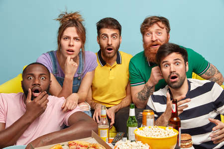 Excited shocked company of friends watch horror film, stare with bugged eyes, hold chin, play video games, eat junk food, drink beer, pose on couch, isolated over blue background. Leisure and rest Banque d'images