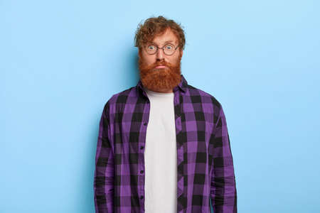 Portrait of handsome bearded red haired man looks surprisingly at camera, wears white t shirt and purple checkered shirt, has embarrassed reaction, isolated on blue background. Facial expressions Фото со стока
