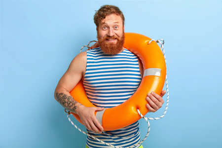 Glad man rescuer poses with orange lifebuoy, wears striped sailor vest, has red hair and beard, rests during summer holiday, has tattoo on arm, isolated on blue background, ready for swimming Foto de archivo