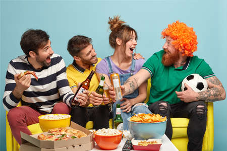 Three happy friends look at funny bearded man in wig, clink bottles of beer, eat pizza, have fun while watch soccer game on televison, being football fans, spend leisure time at home, celebrate goal