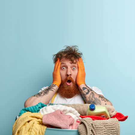Shocked redhead housekeeper faces troublesome situation, keeps both hands on face, has eyes popped out, messy hair, tattooed arms, stands near basin of laundry, models over blue studio wall.
