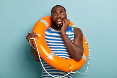 Image of nervous scared man trembles from fear, afraids of swimming without instructor, uses life saving equipment, wears sailor vest, poses over blue background. Athletic frustrated swimmer coach Foto de archivo
