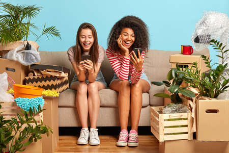 Mixed race women rest on sofa with unpacked boxes around after moving into new house, rent flat together, focused in smartphones, search ideas for apartment design, share news in social networks