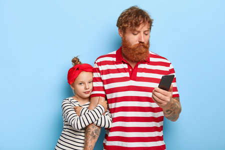 Addicted father uses smartphone, ignores daughter, sends text messages, bored small girl tries attract attention, embraces father hand, wants to play with dad. Parent ignore. Children and fatherhood