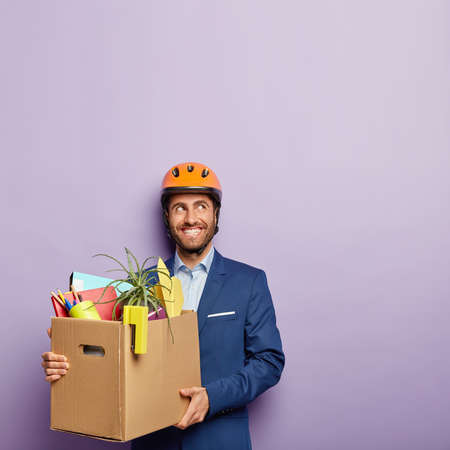 Happy male engineer happy to get new job in office, holds carton box with stationery stuff wears safety orange helmet and blue suit gazes away with delight. People, settling on work, first working day