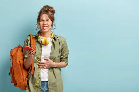 Horizontal shot of dissatisfied woman suffers from cramps in stomach, has diarrhea, being hungry after walking, holds cell phone with headphones, stands with rucksack, frowns face, isolated on blue Banque d'images