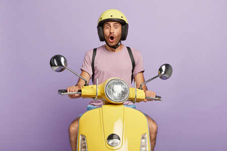 Astonished professional motorcyclist travels on fast transport, shocked with horrible accident on road, drives yellow scooter, wears headgear and purple t shirt. People, driving, reaction, stupor.