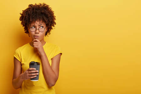 Pensive displeased woman with dark skin, holds chin and looks away, contemplates about something, wears yellow t shirt, holds disposable cup of coffee, smirks face and being upset by bad thoughts Banco de Imagens