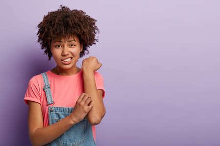 Skin problem concept. Displeased Afro female scratches itchy arm, has allergy, smirks face and looks with dissatisfaction, wears casual pink t shirt and jean overalls, stands against purple wall Foto de archivo