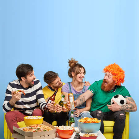 Big group of best friends clink beer bottles, watch football match, celebrate goal, eat pizza, chips, popcorn, have happy faces, sit on comfortable sofa, isolated on blue wall with blank space above