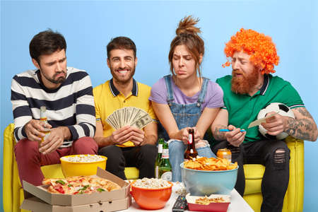 Company of friends watch soccer on TV, one guy makes bet for winning his favourite team, holds money, sit at couch, eat junk food and drink beer. Friendship, sport and entertainment concept. Reklamní fotografie
