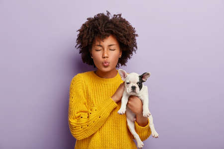 Charming curly haired woman takes care of adorable pet, enjoys pleasure from playing with favourite dog, keeps eyes shut, spends weekend with cute puppy stands over purple background. Domestic animals