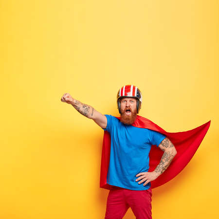 Heroic male character dressed in superhero suit, shouts with courage I am ready to fly, makes flight gesture, saves people, makes world better place, fights against difficulties, poses indoor Reklamní fotografie