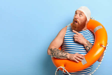 Surprised unshaven male vacationist dressed in bathingcap and striped vest, poses with swimring, points aside with index finger and looks surprisingly aside on blank space for your promotion