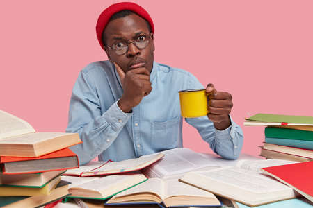 Photo of serious black man holds chin, carries yellow mug of drink, looks directly at camera, wears red hat and shirt, enjoys rest after long hours of reading and studying, isolated over pink wall