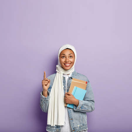 Isolated shot of glad religious woman covers head with veil, carries notepad, points above with fore finger, smiles gladfully, stands over purple wall, blank space for promotion. Islamic girl studies
