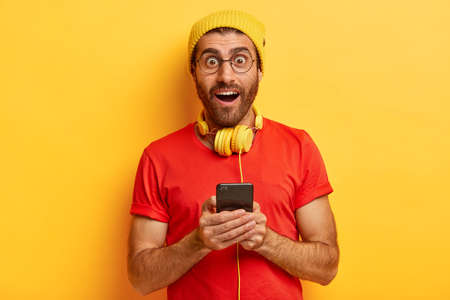 Isolated shot of excited surprised male shocked to get awesome video from friend, surfes web page on smart phone, poses with bated breath, wears yellow hat and red t shirt, connected to headphones