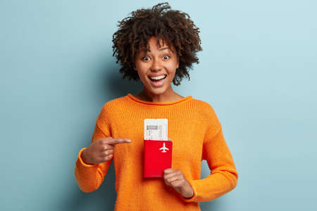 Finally I will have trip abroad. Pleased dark skinned young woman points at passport and boarding pass tickets, ready for air travel flight, wears casual bright jumper, isolated over blue background